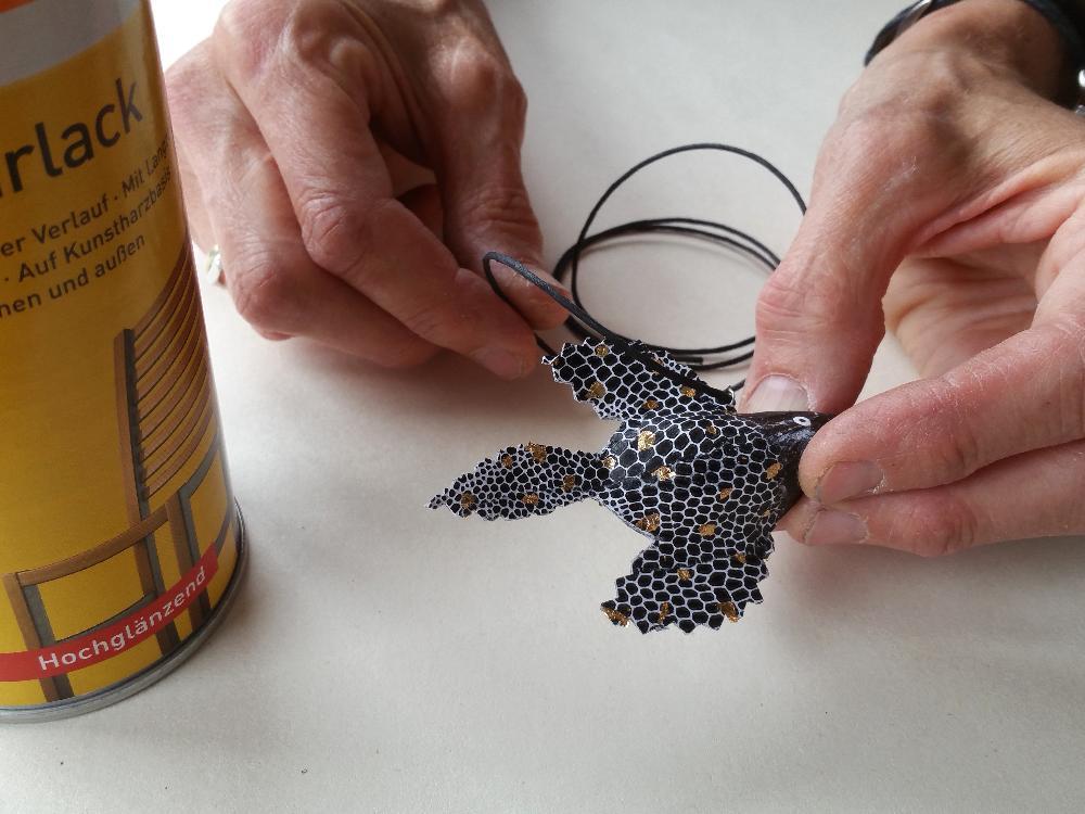Zum Schluss fädel ich eine Papierschnur durch die Öse und lackiere den Fisch.